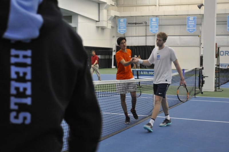 Sophomore Simon Soendergaard shakes hands with his Virginia Tech opponent in the Cone-Kenfield Tennis Center on March 2.