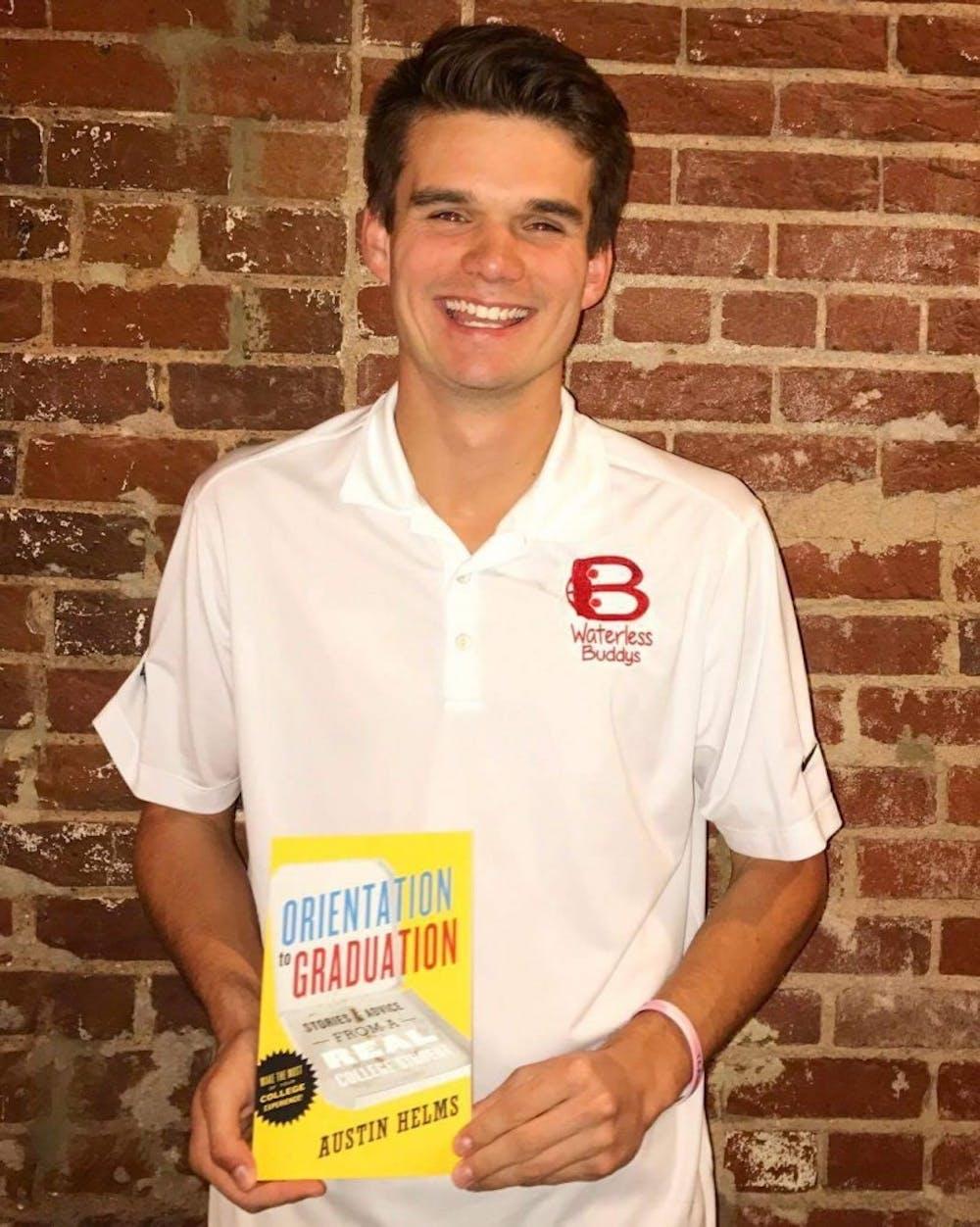 "<p>2016 graduate Austin Helms poses with his book, ""Orientation to Graduation."" Photo courtesy Austin Helms.</p>"