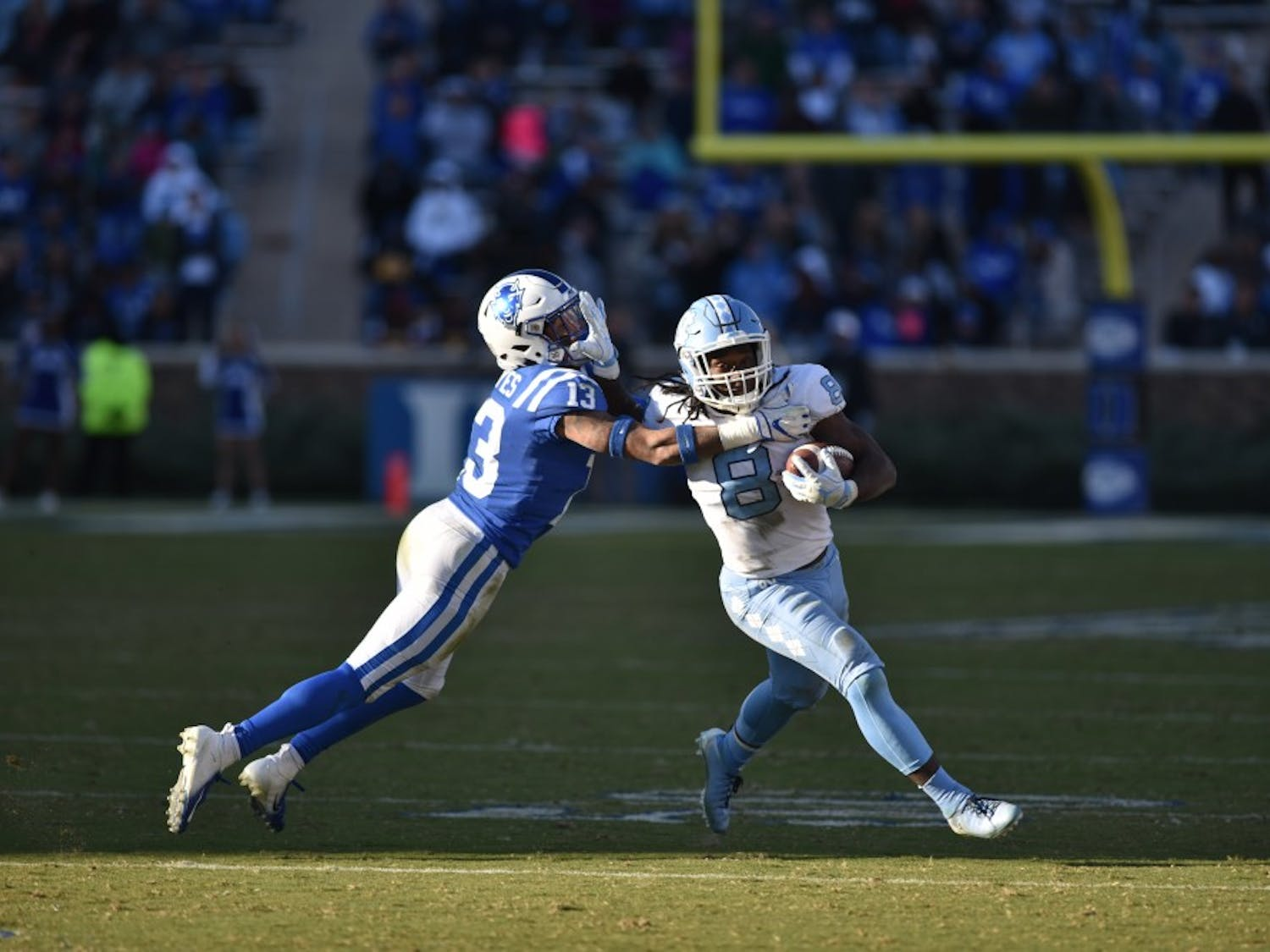 Sophomore tailback Michael Carter (8) stiff arms a Duke defender. Duke defeated UNC 42-35 on Saturday Nov 10 at Wallace Wade Stadium in Durham.