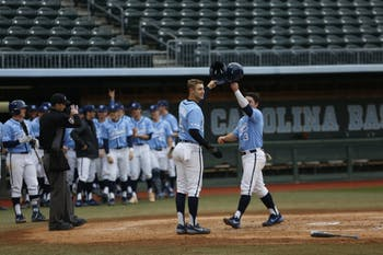 Brandon Martorano (4) and Dylan Harris (3) celebrate after a home run by Michael Busch in UNC's 11-8 loss over VCU on Wednesday, Feb. 27, 2019.