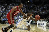 Lorenzo Brown and Harrison Barnes dive for a loose ball during the first half of play. The Tar Heel forward scored 16 points during the game.
