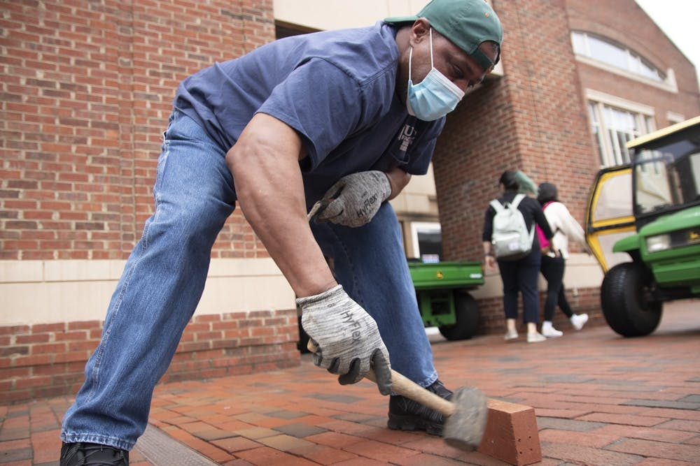 <p>UNC staff member Walter Thompson fills in missing bricks next to Rams Head Recreation Center on Friday, Mar. 26, 2021. Thompson spends every weekday searching for missing bricks on campus to replace them.</p>