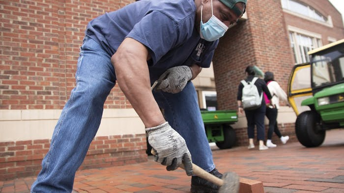 UNC staff member Walter Thompson fills in missing bricks next to Rams Head Recreation Center on Friday, Mar. 26, 2021. Thompson spends every weekday searching for missing bricks on campus to replace them.