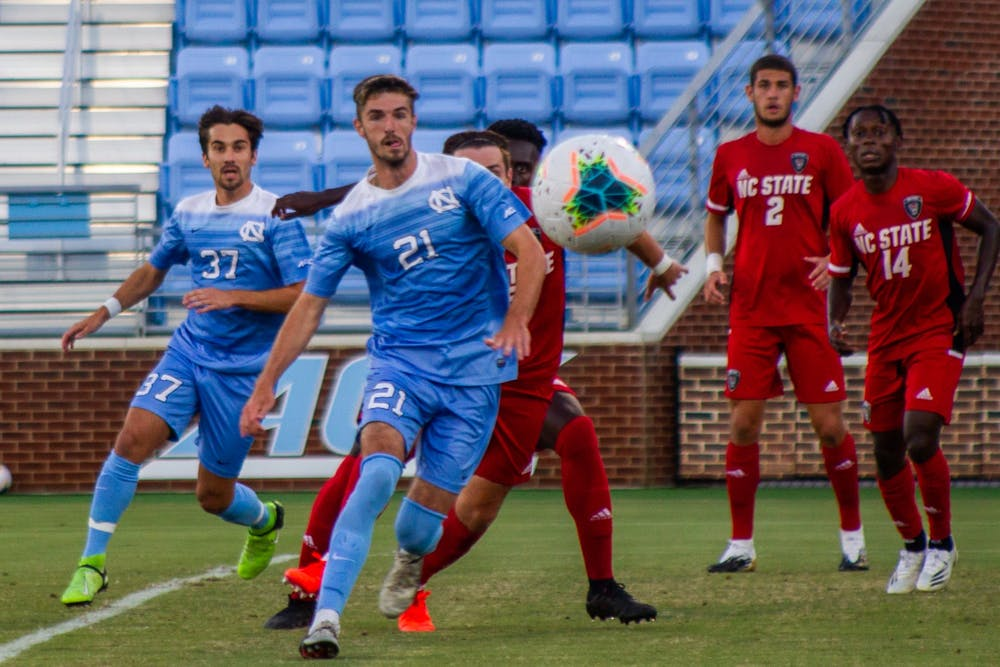<p>UNC senior forward Alex Rose (21) and junior midfielder Jacques Bouvery (37) prepare to kick the ball after a corner kick during the scrimmage against NC State on Sunday Sept. 20 2020. UNC won 1-0.</p>