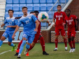 UNC senior forward Alex Rose (21) and junior midfielder Jacques Bouvery (37) prepare to kick the ball after a corner kick during the scrimmage against NC State on Sunday Sept. 20 2020. UNC won 1-0.