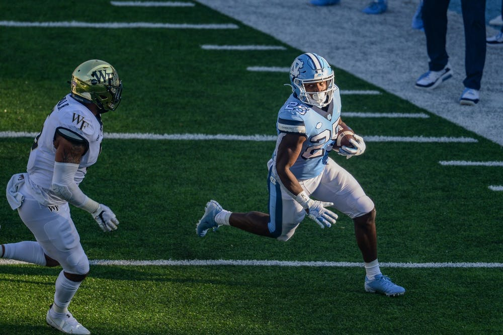 UNC's junior running back Javonte Williams (25) evades members of Wake Forest's defensive line during a game in Kenan Memorial Stadium on Saturday, Nov. 14, 2020. UNC beat Wake Forest 59-53.