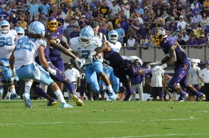 UNC tailback Jordon Brown (2) pushes through ECU players on Saturday at Dowdy-Ficklen Stadium.