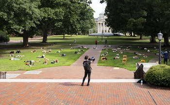 Hồng-Ân Trương, a UNC associate professor in the Department of Art and Art History speaks to the crowd of socially-distanced students and community members laying on the ground as part of the Die-In protest on Wednesday, Aug. 5, 2020. The protest called for UNC to transition to fully remote classes for the Fall 2020 semester after a letter of caution sent to Chancellor Guskiewicz by the Orange County Health Director Quintana Stewart.