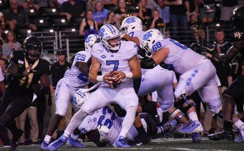 UNC-CH first-year quarterback Sam Howell (#7) runs the football while his teammates block the Wake Forest defense behind them.