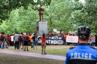 Police watch over a group of protestors near the Silent Sam statue during a demonstration on Thursday afternoon.