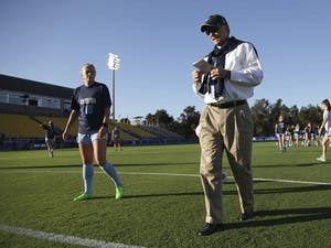 UNC women's soccer head coach Anson Dorrance looks over his notes as he walks around at practice.