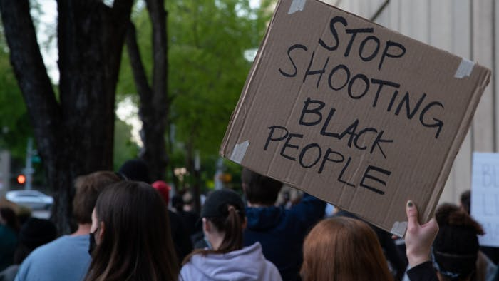 A demonstrator holds a sign at a community demonstration in Raleigh, North Carolina on April 23, 2021.