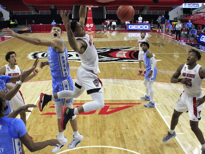 N.C. State's Shakeel Moore (2) slams in two in the second half during N.C. State's 79-76 victory over UNC at PNC Arena in Raleigh, N.C., Tuesday, December 22, 2020. Photo courtesy of Ethan Hyman.