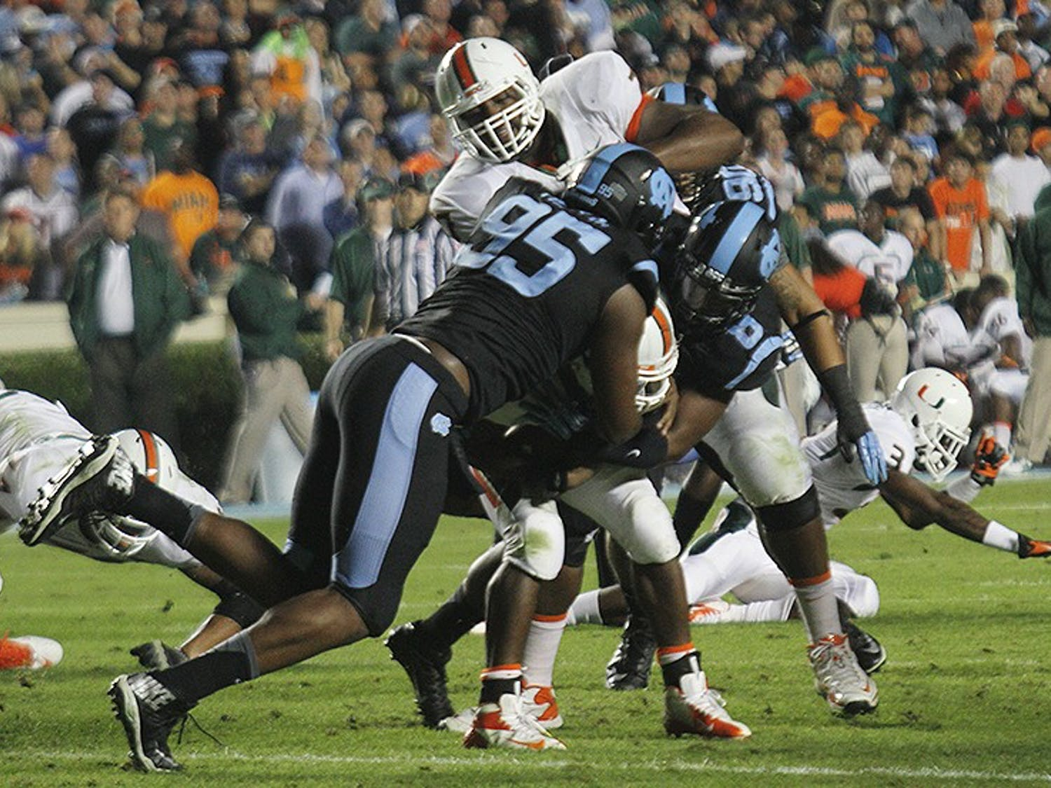 Kareem Martin (95), a senior defensive end, assists a teammate in tackling a player during the game against Miami on Oct. 17. Martin won the ACC's defensive lineman of the week for his performance.