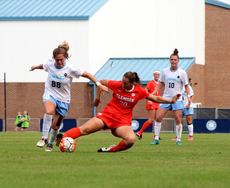 Alexa Newfield (88) keeps the ball away from Clemson player Jenna Weston (20).