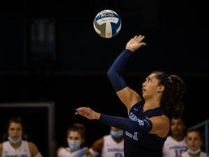 In the Sept. 18 game against Davidson, junior libero and defensive specialist Karenna Wurl (21) serves the ball. UNC won three out of three sets.