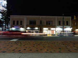 Cars drive on Franklin Street at night on Sunday, Feb. 16, 2020 before the COVID-19 pandemic. Now, the pictured businesses and many others on Franklin Street have either ceased operations entirely or have adapted their operations for the current crisis.