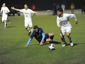 James Madison midfielder Niclas Mohr (5) dribbles past midfielder Jeremy Kelly (29) during Sunday's NCAA tournament game vs. James Madison. The Tar Heels lost 2-1.