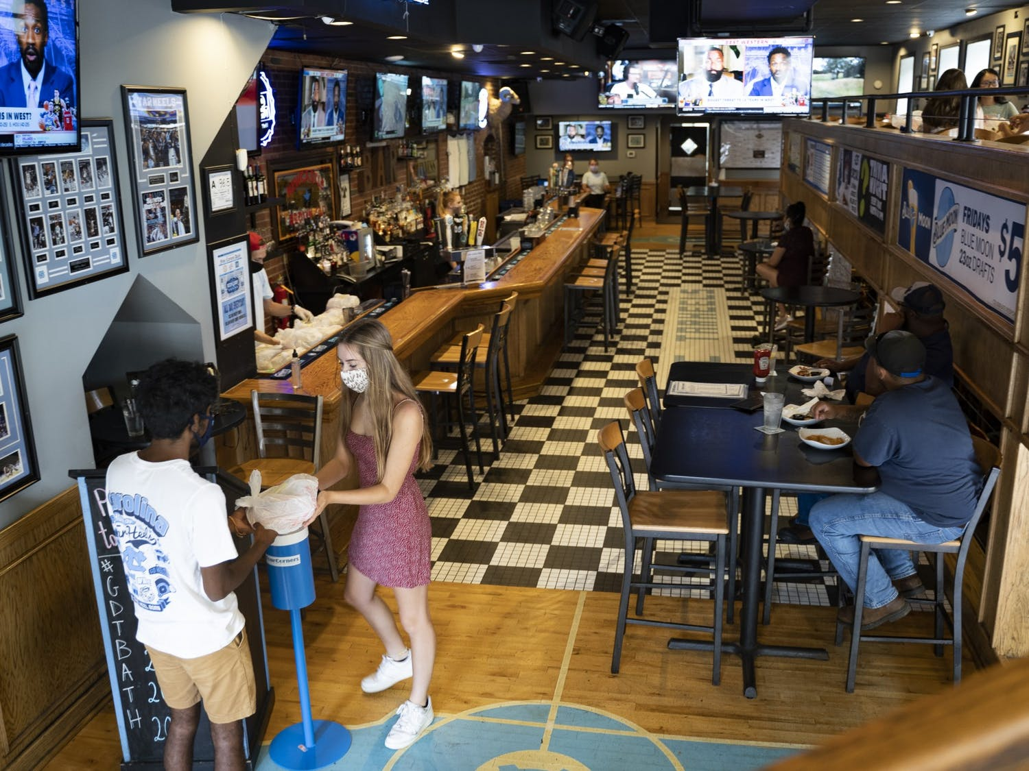 A customer receives his take-out order from Four Corners on Franklin Street on Thursday, Aug. 6, 2020. Game day restaurants like this one have seen and will likely continue to see much less traffic than normal due to COVID-19's impact on dining and sports.