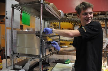 UNC first-year student and Cosmic Cantina employee Samuel Finlay makes a burrito on Thursday, Mar. 21. Starting Apr. 2, Cosmic will increase its prices by 9% in order to support rising food costs and employee wages.