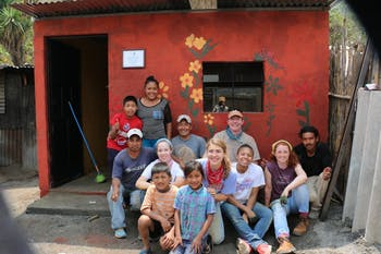 Nikita Billman, along with other volunteers, two professional workers, and the Guatemalan family pose in front of their newly constructed homes. Photo by Vic Cocowitch.