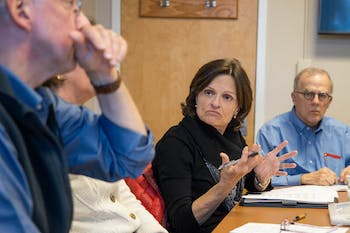 Committee members Suzanne Gulledge (center) and Michael Smith (right) react as Secretary Vincas Steponaitis (left) leads the UNC Faculty Committee on University Governance meeting. The committee met on Wednesday, January 8, 2020 in Carr Building.