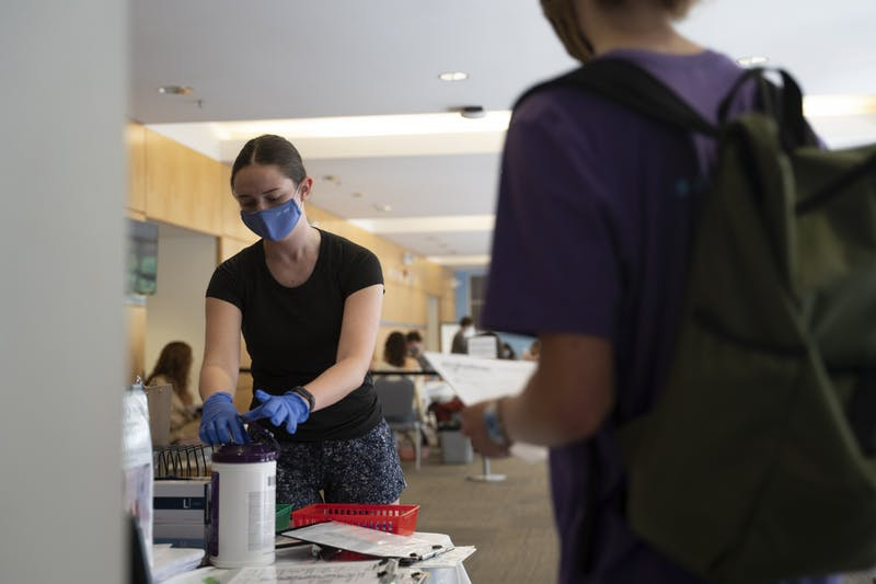 A volunteer sanitizes her hands while a student waits in line to hand in her form in the Student Union on Wednesday, Oct. 7, 2020.