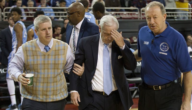 North Carolina head coach Roy Williams is escorted off the court by head athletic trainer Doug Halverson, left, and game staff early in the second half against Boston College on Tuesday, Feb. 9, 2016, at Conte Forum in Chestnut Hill, Mass. Williams appeared to faint and sat on the floor surrounded by players during the time out, and had trouble getting to his feet, before being assisted off the court. Assistant coach Steve Robinson took over in Williams absence as play resumed. (Robert Willett/Raleigh News & Observer/TNS)