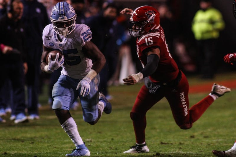 North Carolina State junior linebacker Calvin Hart Jr. (15) attempts to tackle sophomore running back Javonte Williams (25). UNC defeated NC State 41-10.
