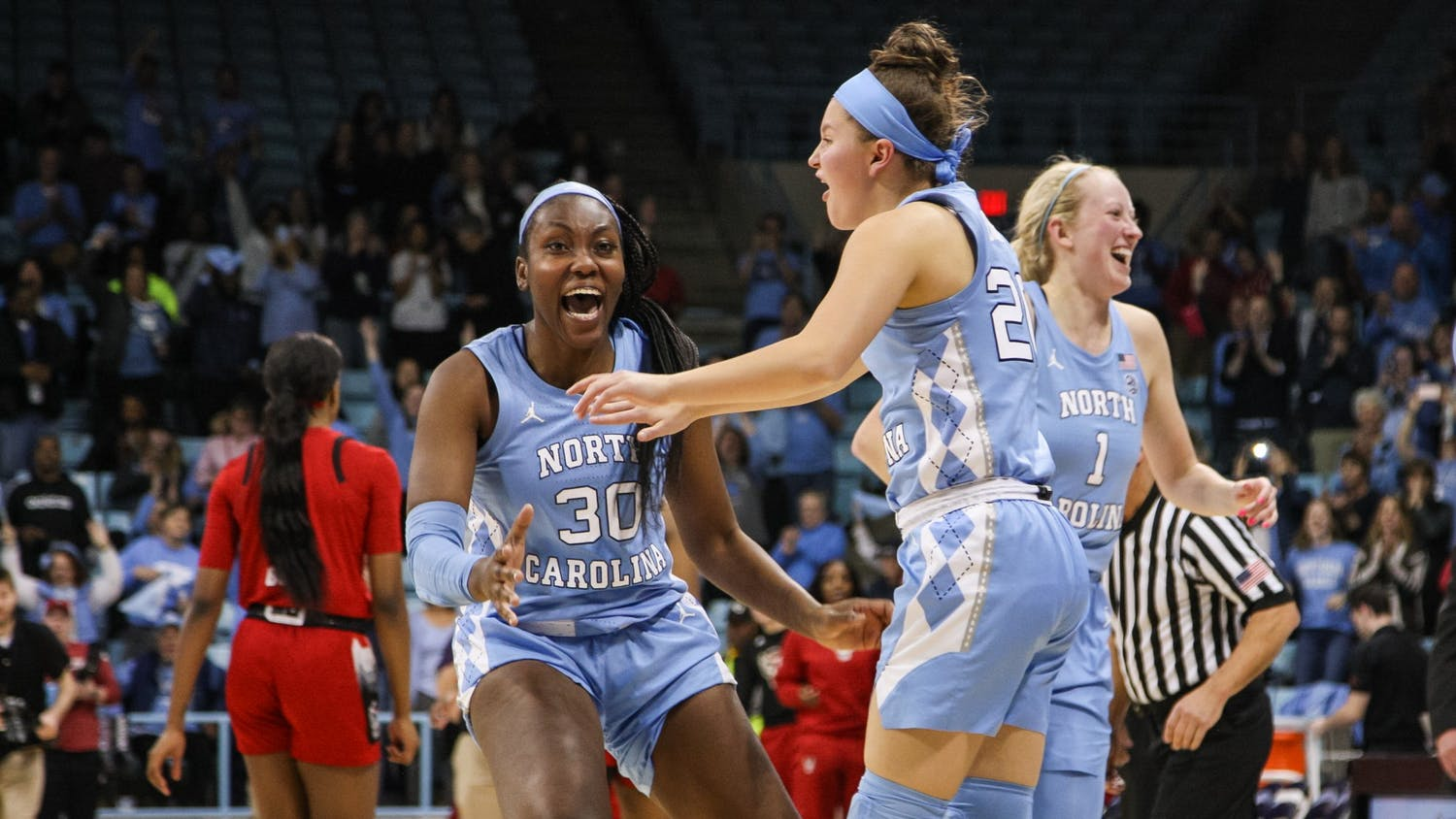 UNC players Janelle Bailey (30), Leah Church (20), and Taylor Koenen (1) celebrate UNC's win over N.C. State on Thursday, Jan. 9, 2020. UNC broke NC State's undefeated streak with a score of 66-60.