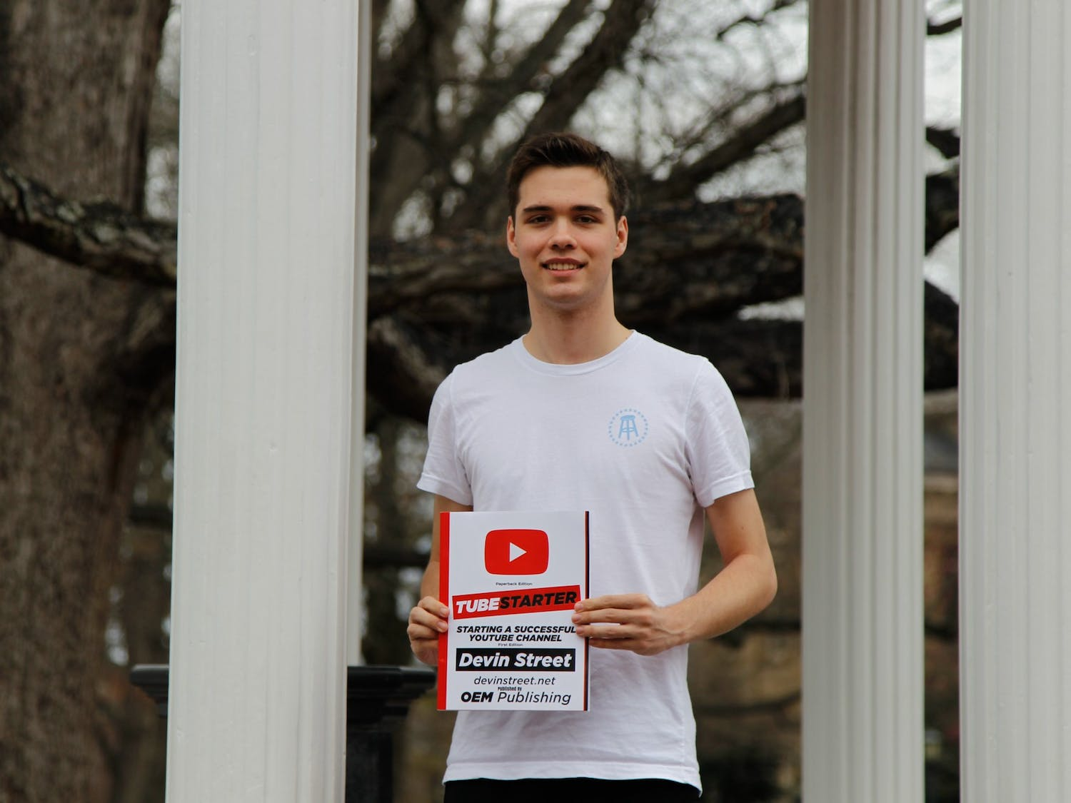 """Devin Street, a first-year business major, poses for a portrait at the Old Well with his book, TubeStarter: Starting A Successful YouTube Channel, on Wednesday, Feb. 26, 2020. Street says, """"The biggest privilege kids have today is the opportunity to do big things because of advancements in technology and the internet. Whether it's publishing a book or starting a business, it can all be done on a phone or laptop.""""."""