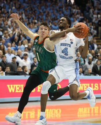 Miami junior guard Dejan Vasiljevic (1) attempts to block UNC junior guard Brandon Robinson (4) during overtime on Saturday, Feb. 9, 2019 in the Smith Center. UNC men's basketball defeated Miami 88-85 in overtime.