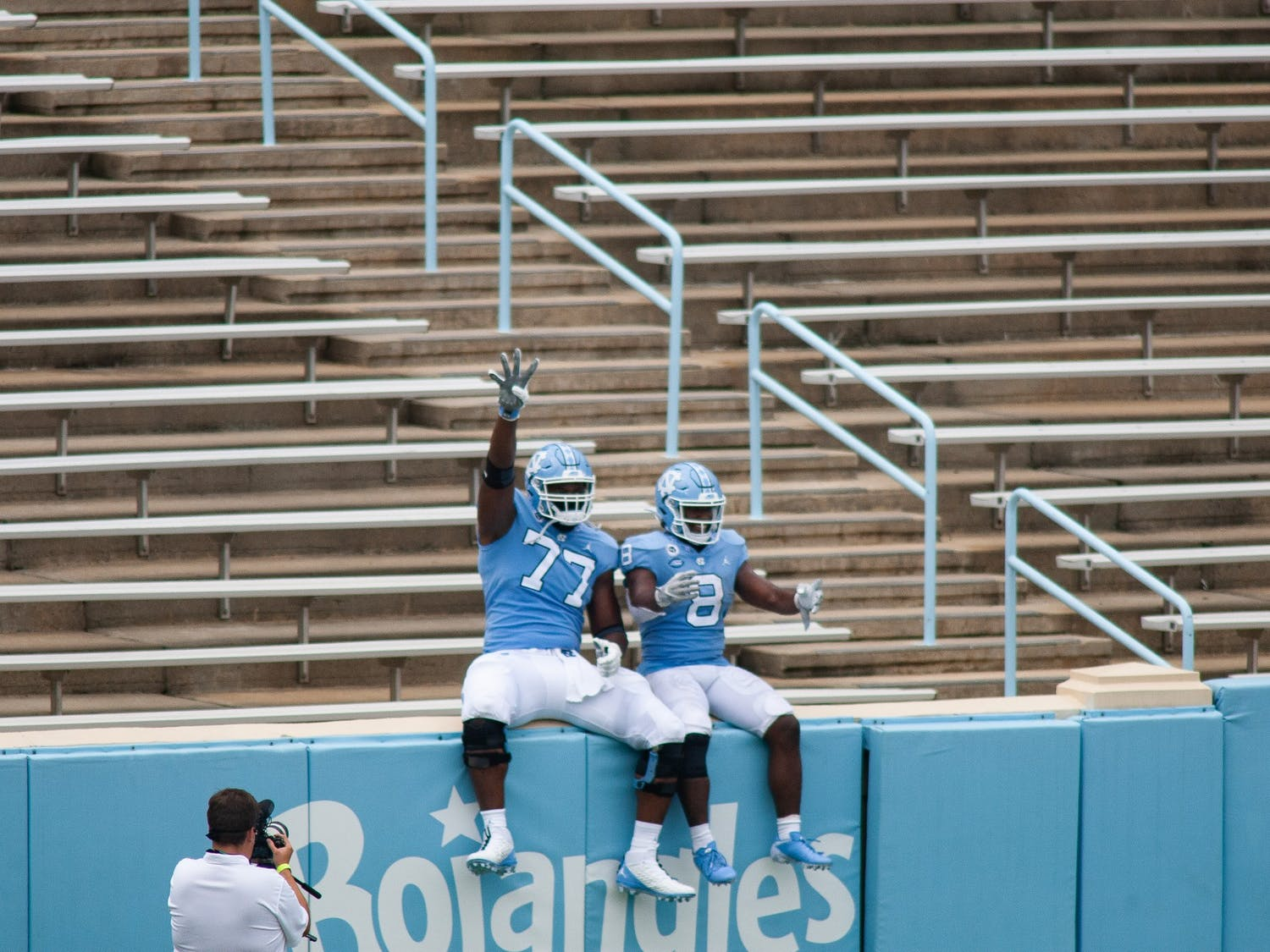 UNC senior running back Michael Carter (8) and and redshirt first year offensive lineman Wisdom Asaboro (77) lead a cheer from the empty student section of Kenan Memorial  Stadium before the beginning of the fourth quarter during a game against Syracuse ion Saturday, Sept. 12, 2020. UNC beat Syracuse 31-6.