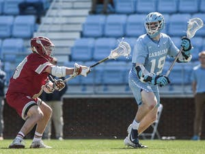 UNC first-year attackman Brian Cameron (19) fends the ball against Denver midfielder Danny Logan (19) during UNC's 12-10 home loss against the University of Denver on Saturday, March 3, 2019 at the UNC Soccer and Lacrosse Stadium in Chapel Hill, N.C. This was the UNC Men's Lacrosse team's inaugural game at the UNC Soccer and Lacrosse Stadium.