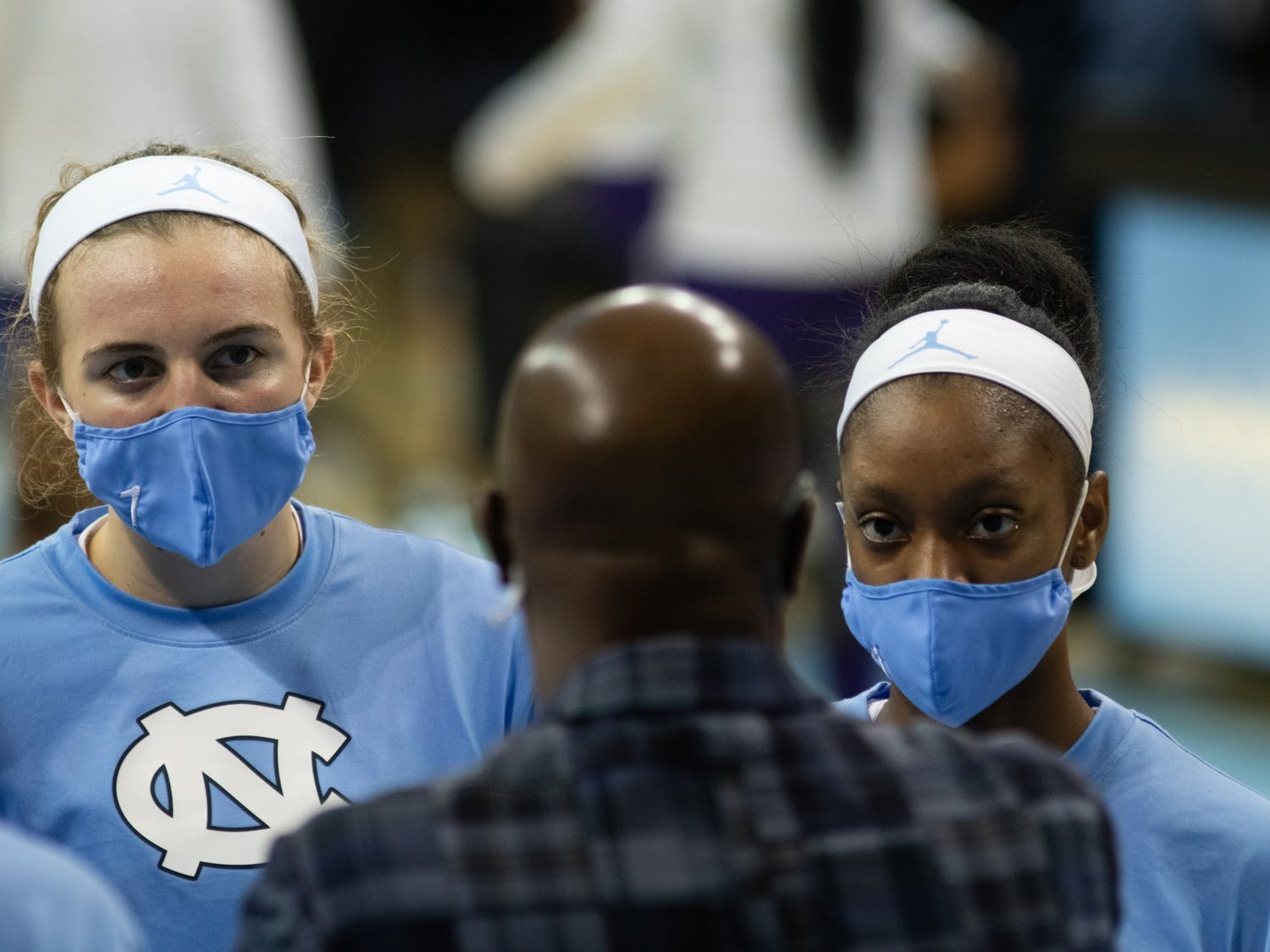 UNC first year forward Alyssa Utsby (1) and sophomore guard Kennady Tucker (4) listen to assistant coach Adrian Walters prior Carolina's 95-70 victory over High Point at Carmichael Arena, November 29, 2020.