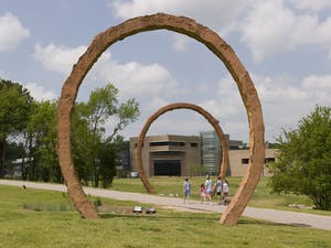 """Visitors walk by Thomas Sayre's sculpture """"Gyre"""" at the North Carolina Museum of Art. The museum, among other organizations, has taken to social media to promote the arts. Photo courtesy of Kat Harding."""