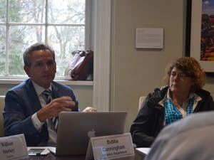 UNC Athletic Director Bubba Cunningham and Jaye Cable discuss the minutes during the Faculty Executive Committee Meeting on Tuesday, Sept. 10, 2019.
