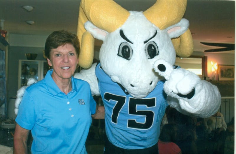 Beth Miller posing with Rameses, the mascot of UNC Athletics, in the home of former fencing head coach Ron Miller.  Photo courtesy of UNC Athletic Communications.
