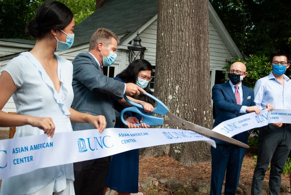 Chancellor Kevin M. Guskiewicz and Heidi Kim, the director of the Asian American Center, cut the ribbon to officially open the UNC Asian American Center.