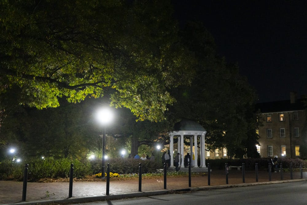 <p>A group of students crowd at the Old Well on Saturday, Oct. 31, 2020.</p>