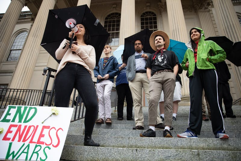 """Ava Erfani (left), a political science major, addresses a crowd from the steps of Wilson Library during a """"No War with Iran"""" protest on Monday, Jan. 13, 2020. """"Our entire culture is based around this idea of taarof, a valuing of friendship and showing your appreciation for other people,"""" said Erfani, whose family came from Iran. """"It's a big reason why it upsets me so much to see politicians talking about a place like that as expendable or evil."""""""