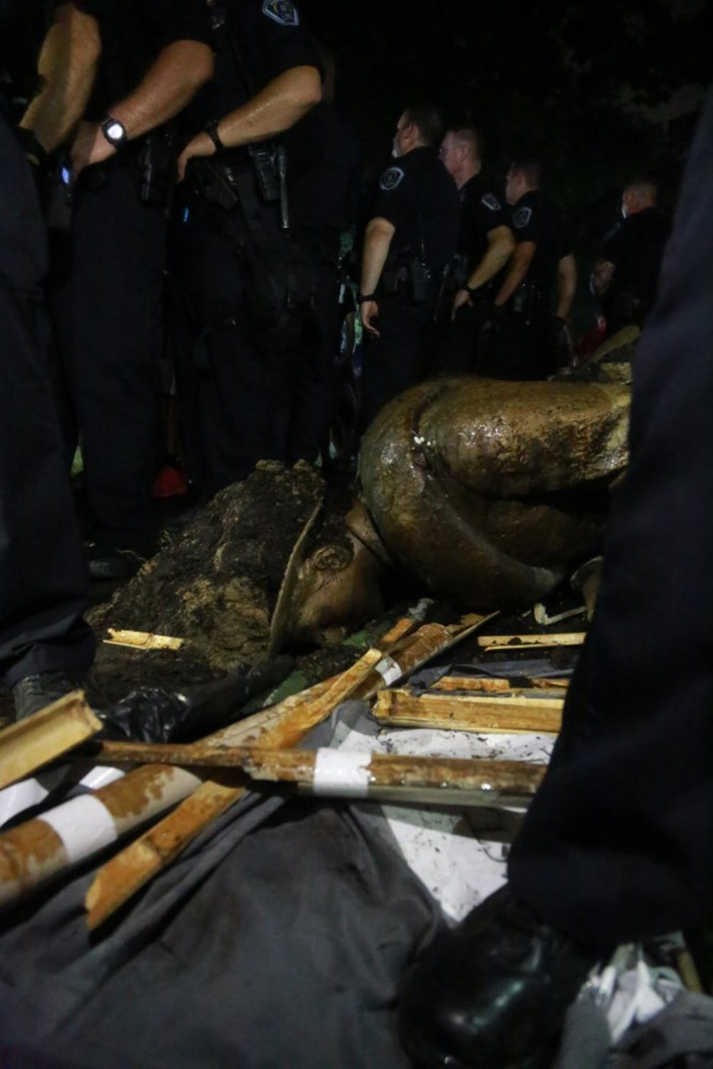 <p>The just-toppled confederate monument, Silent Sam, lays face-down on the ground as Chapel Hill police officers surround it and block out the crowd on Monday, August 20, 2018.</p>