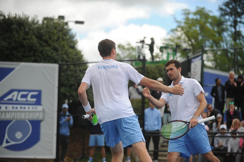 Junior William Blumberg high-fives his doubles partner senior Blaine Boyden at the ACC tournament semifinals. UNC played against Virginia and lost 3-4.