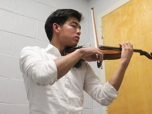 """Junior biology major Thoai Vu practicing the violin in Hill Hall on Tuesday, Oct. 22, 2019. Vu is the president and founder of Heeling in Harmony. Vu said that the club """"aims to promote healing and improve quality of life through music and music related activities."""""""
