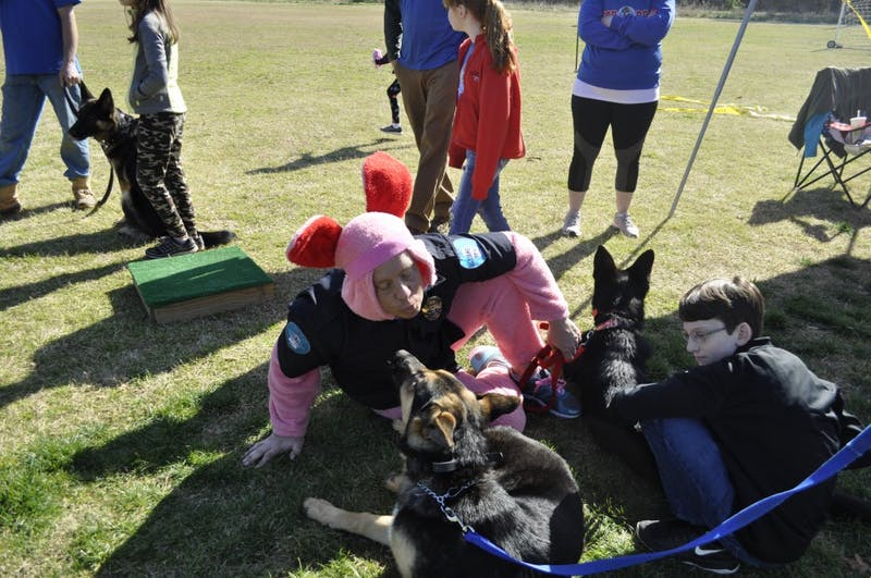 Lt. Andy Simmons leans in for a kiss at the Dog Easter Egg Hunt at Gold Park in Hillsborough Saturday morning