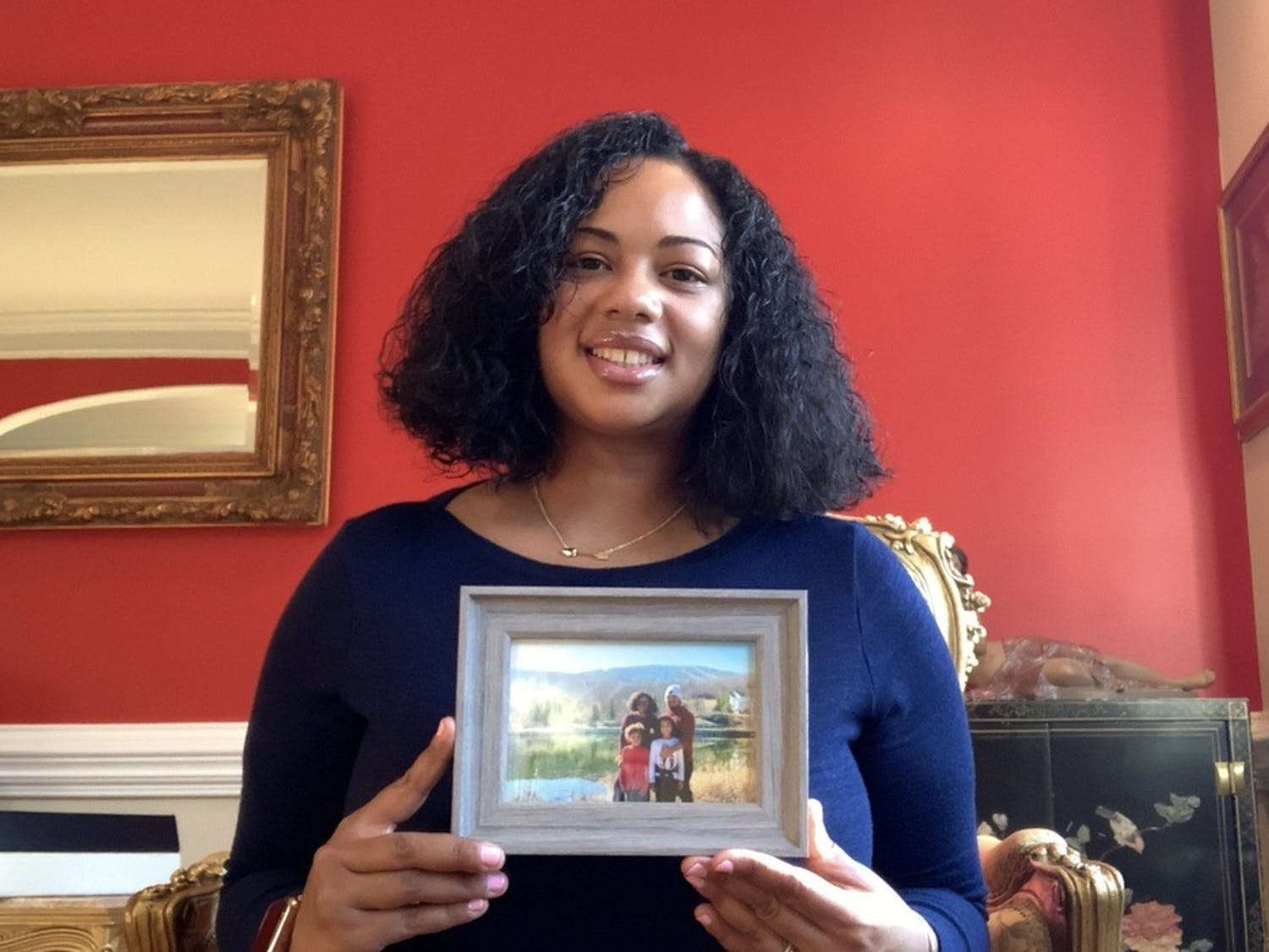 Jackie Carr-Martinez poses for a virtual portrait with a photo of her family in her home in Greensboro on Feb. 23, 2021. Carr-Martinez, who identifies as African-American, Indian and Guyanese, was afraid to return to the hospital after a painful experience with a white doctor the night before her first child's birth.
