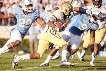 Damien Washington (29) and Travis Hughes (9) try to tackle a Georgia Tech player.