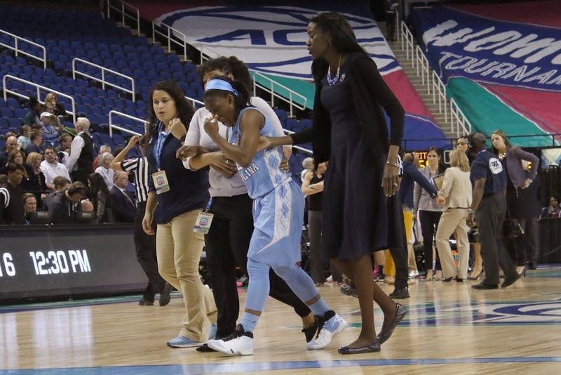 Carolina guard Jamie Cherry (10) is helped off the court after tweaking her knee in the fourth quarter of Wednesday's game. The Tar Heels fell to the University of Pittsburgh 82-72 in overtime in the opening round of the ACC tournament.