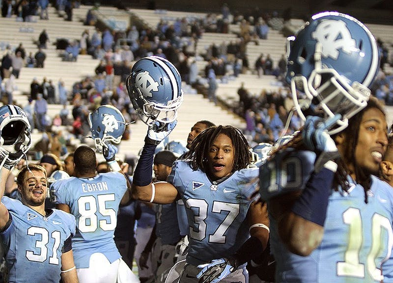 North Carolina players Pete Mangum, T.J. Jiles and Tre Boston, from left to right, hold their helmets aloft during the fight song after the game, the team's last of the season.