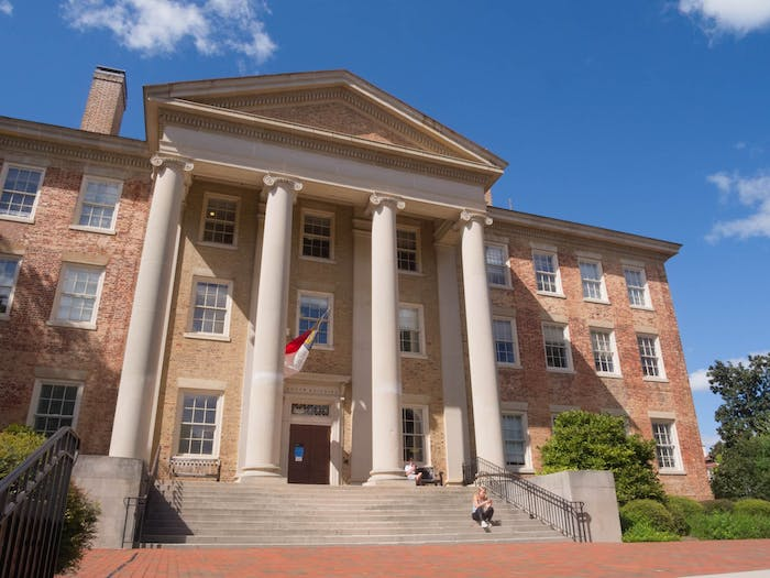 People sit on the steps and benches in front of South Building on Sunday, Sept. 12, 2020.